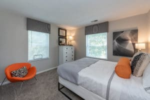 white bed in a bedroom with an orange chair