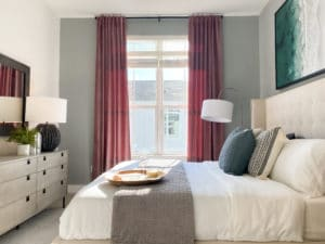A white bed with a window behind it with red curtains