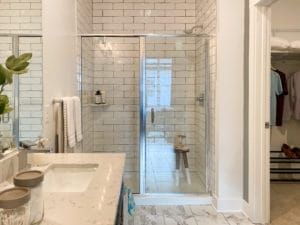 A white tiled stand up shower with a vanity in the foreground