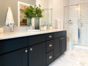 A dual vanity with black cabinets and white tile