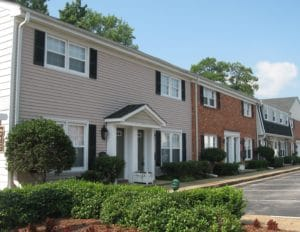 The tan vinyl and red brick exterior of Walker's Chase townhomes