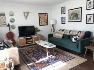 Green couch with picture of elephant above it